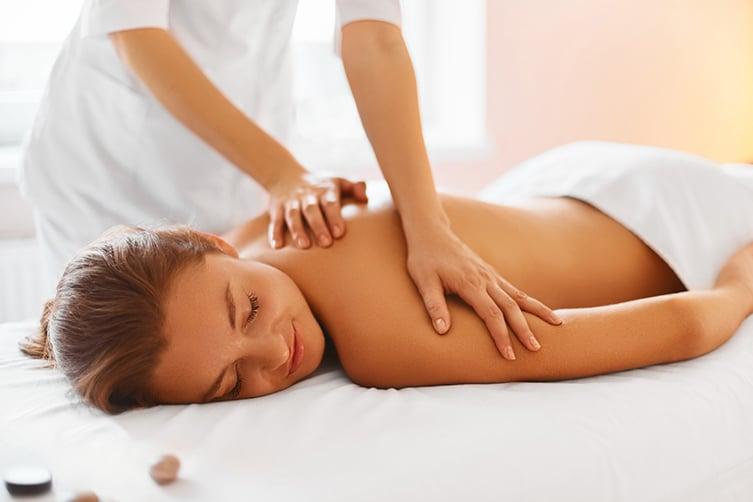 Massage du dos en institut de beauté avec des huiles Bio